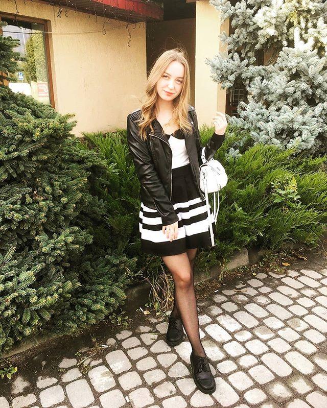 Веселая блондинка в кожаной куртке на фоне сада