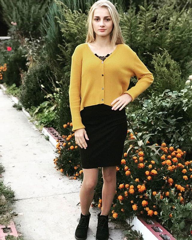 Блондинка в черной юбке прогуливается по алее