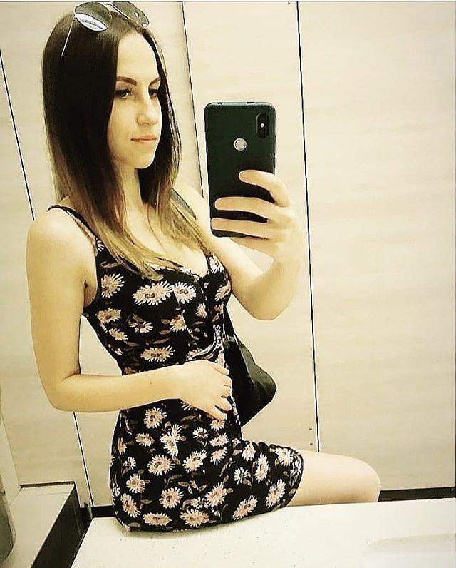 Длинноволосая девчонка делает селфи в платье